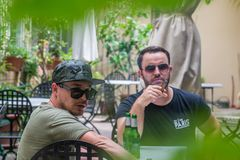 Two albanian mafia guys are smoking and drinking. Two albanian guys are dressed with a green and black t-shirt and blue jeans, green hat and black sunglasses royalty free stock photo
