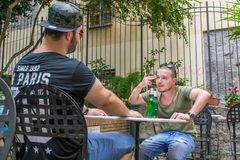 Two albanian mafia guys are talking about killing someone. Two albanian guys are dressed with a green and black t-shirt and blue jeans, green hat and black stock photo