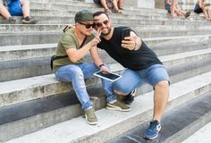 Two albanian guys are taking a selfie. Two albanian guys are dressed with a green and black t-shirt and blue jeans, green hat and black sunglasses. They are royalty free stock images