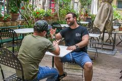 Two albanian mafia guys are talking business. Two albanian guys are dressed with a green and black t-shirt and blue jeans, green hat and black sunglasses. They stock photo