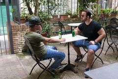 Two albanian mafia guys are talking business. Two albanian guys are dressed with a green and black t-shirt and blue jeans, green hat and black sunglasses. They stock images