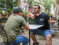Two albanian mafia guys are talking about murdering someone. Two albanian guys are dressed with a green and black t-shirt and blue jeans, green hat and black royalty free stock photography