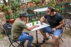 Two albanian mafia guys are talking about petty bulshit. Two albanian guys are dressed with a green and black t-shirt and blue jeans, green hat and black royalty free stock photos