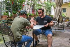 Two albanian mafia guys are talking about petty bulshit. Two albanian guys are dressed with a green and black t-shirt and blue jeans, green hat and black royalty free stock photography