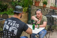 Two albanian mafia guys are about to get in a fight with a bottle. Two albanian guys are dressed with a green and black t-shirt and blue jeans, green hat and stock photo