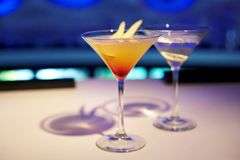 Two alcohol cocktails on the table. In restaurant on blue background Royalty Free Stock Photography