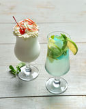 Two alcohol margarita martini cocktail and milkshake composition Royalty Free Stock Photo