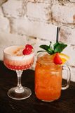 Two alcoholic cocktails garnished with berries against the white. Two fruity alcoholic cocktails garnished with berries against the white brick background stock image