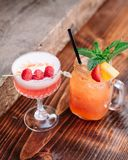 Two alcoholic cocktails garnished with berries and mint. Two fruity alcoholic cocktails garnished with berries and mint on a wooden table outside stock photos