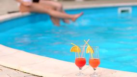 Two cocktails on the background of pool with girls. Two alcoholic orange drinks stand on the background of a small pool in the hotel. In the background a blurred stock video