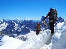 Two alpinists and mountaineer climber on Aiguille du Midi. CHAMONIX MONT BLANC french ALPS, top alpine mountains range landscape, FRANCE with clear blue sky in Stock Photos