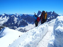 Two alpinists and mountaineer climber on Aiguille du Midi. CHAMONIX MONT BLANC french ALPS, top alpine mountains range landscape, FRANCE with clear blue sky in Royalty Free Stock Photo