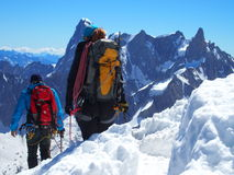Two alpinists and mountaineer climber on Aiguille du Midi. CHAMONIX MONT BLANC french ALPS, top alpine mountains range landscape, FRANCE with clear blue sky in Stock Photography