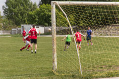 Two amateur football teams play on the field in Stock Photography
