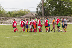 Two amateur football teams play on the field in Royalty Free Stock Photos