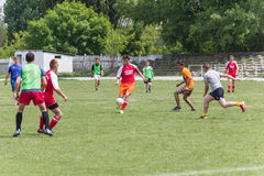 Two amateur football teams play on the field in Royalty Free Stock Image