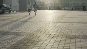 Two amateur runners crossing town square during morning jog, active lifestyle
