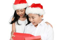 Two amazed children open Christmas presents. Photo of two amazed children open Christmas presents box together while wearing Santa hat, isolated on white Stock Image