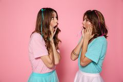 Two amazed girls in colorful tshirts touching their cheeks and l Stock Photo