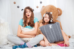 Two amazed lovely sisters sitting and hugging pillow Royalty Free Stock Photography