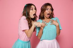 Two amazed pretty girls dressed like princess pointting with fin. Ger, looking aside, isolated over pink background Stock Photography