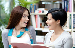 Two amazed students read at the library Stock Photo