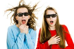 Two amazed teen girls in cinema wearing 3D glasses experiencing 5D cinema effect - wind blowing into faces royalty free stock images