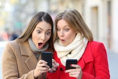 Two amazed women finding content on phones. Front view portrait of two amazed women finding on line content on their smart phones on the street in winter Royalty Free Stock Photography