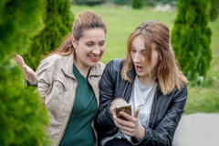 Two amazed women friends sharing social media outdoor Stock Image