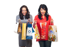 Two amazed women about their shoppings. Two women looking amazed in their shopping bags isolated on white background Stock Photography