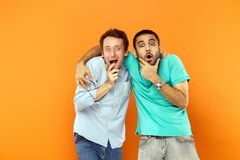 Two Amazement friends hugging, holding his chin and looking at c Royalty Free Stock Image