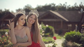 Two amazing girls in a long gowns and crowns. Two amazing girls in long gowns and crowns laughing in the park with roses stock video footage