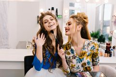Two amazing joyful models having fun together in haidresser salon. Preparing to party, expressing true positive emotions. Two amazing joyful models having fun royalty free stock images