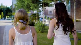 Two amazing women wearing white dresses are walking down an alley and peacfully talking about something. Two amazing women wearing white dresses are walking down stock footage