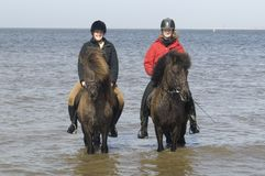 Two amazones on horseback on the beach Stock Image