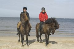 Two amazones on horseback on the beach Stock Images