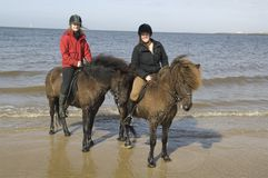 Two amazones on horseback on the beach Stock Photos