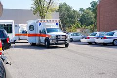 Two ambulances at the scene of a medical emergency. Ambulances and police at the scene of a medical emergency in a parking lot Stock Photo