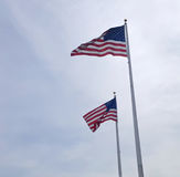 Two American Flags Flying In The Wind. Against a cloudy white sky Royalty Free Stock Image