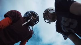 Two American football players discussing tactics. Low angle view of two male American football players discussing game tactics stock video