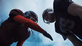 Two American football players discussing tactics. Low angle view of two male American football players discussing game tactics Royalty Free Stock Images