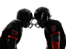 Two american football players face to face silhouette. Two american football players face to face in silhouette shadow on white background Stock Image