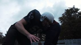 Two American football players hitting each other. Low-angle side view of two American football players hitting each other by accident during match outdoors stock footage