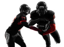 Two american football players passing play action silhouette royalty free stock photo