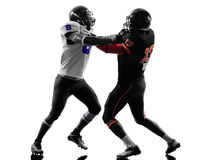Two american football players on scrimmage holding. In silhouette shadow white background Royalty Free Stock Image