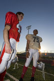Two American football players standing on pitch at sunset, low angle view (lens flare, tilt) Stock Photo
