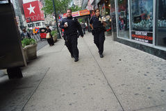 Two american police officers patrolling in new york, usa. New York, USA - November 13, 2008: two american police officers, policeman and policewoman or man and Royalty Free Stock Images