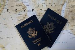 Passports on a map of Egypt. Two American traveling passports on a road map of Egypt travel destination stock photos