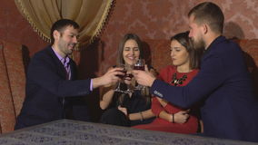 Two amorous couples celebrating together at restaurant. Two happy smiling young couples with champagne at celebration stock video footage
