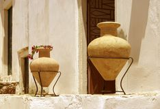 Two amphoras. Two clay amphorae against light colored stone wall stock images
